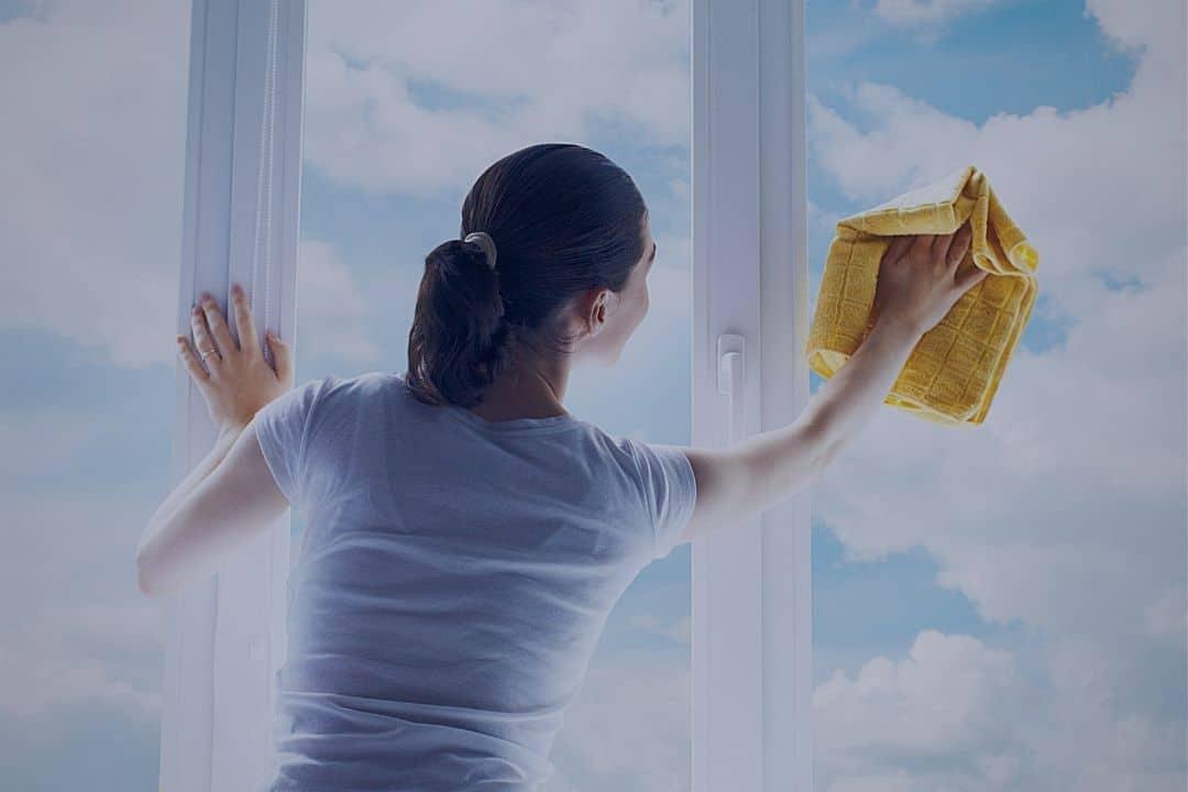 woman washing window on cloudy day