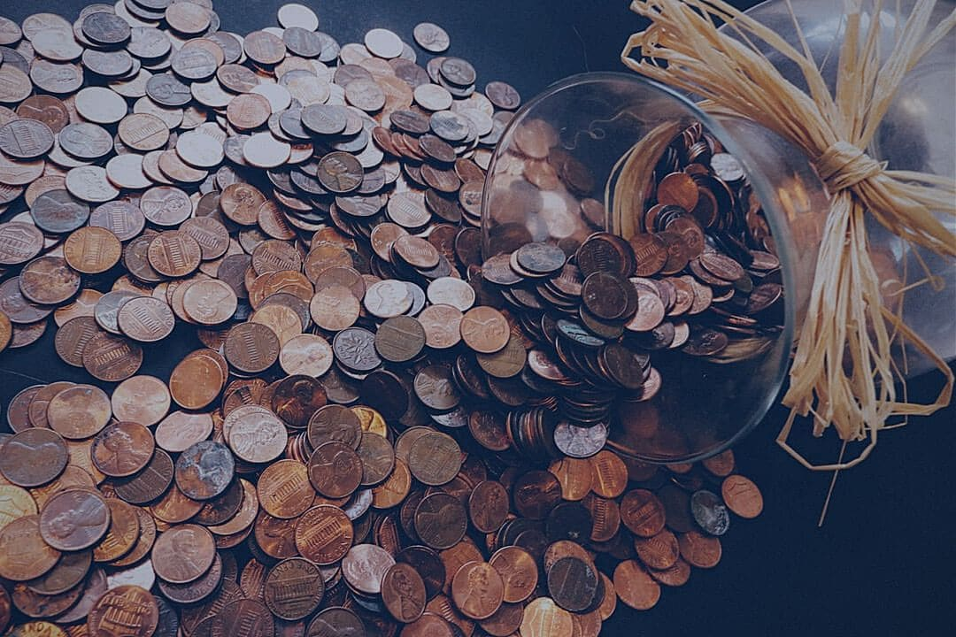 Coins spilling out of a jar and onto a table