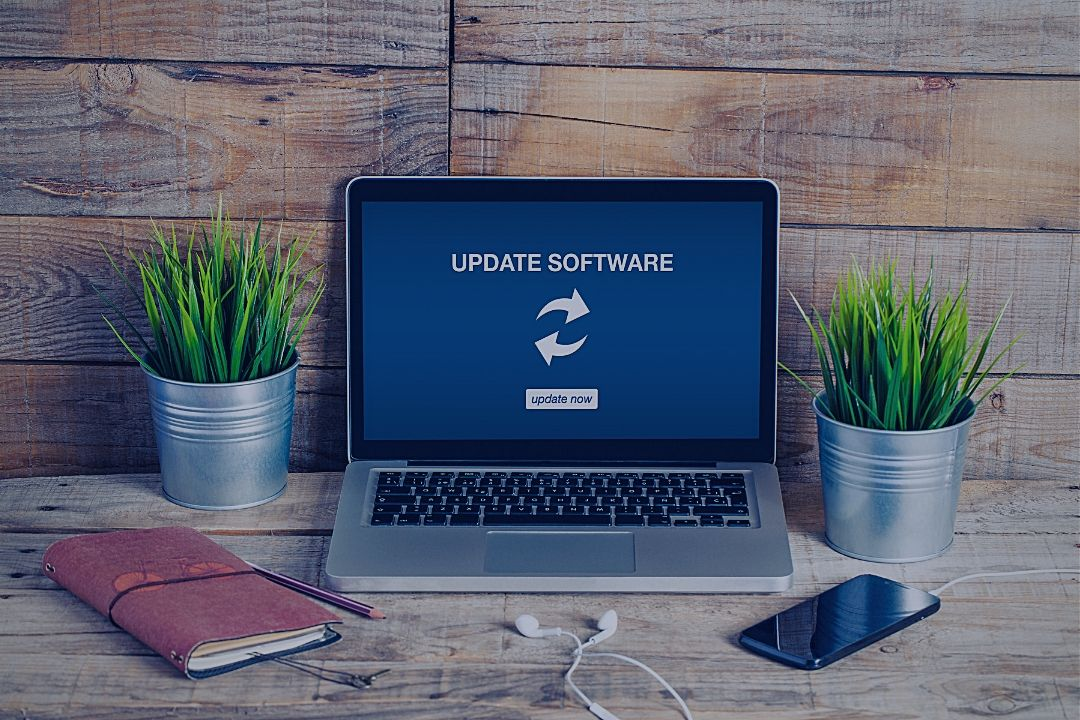 Laptop on desk, updating software message on screen