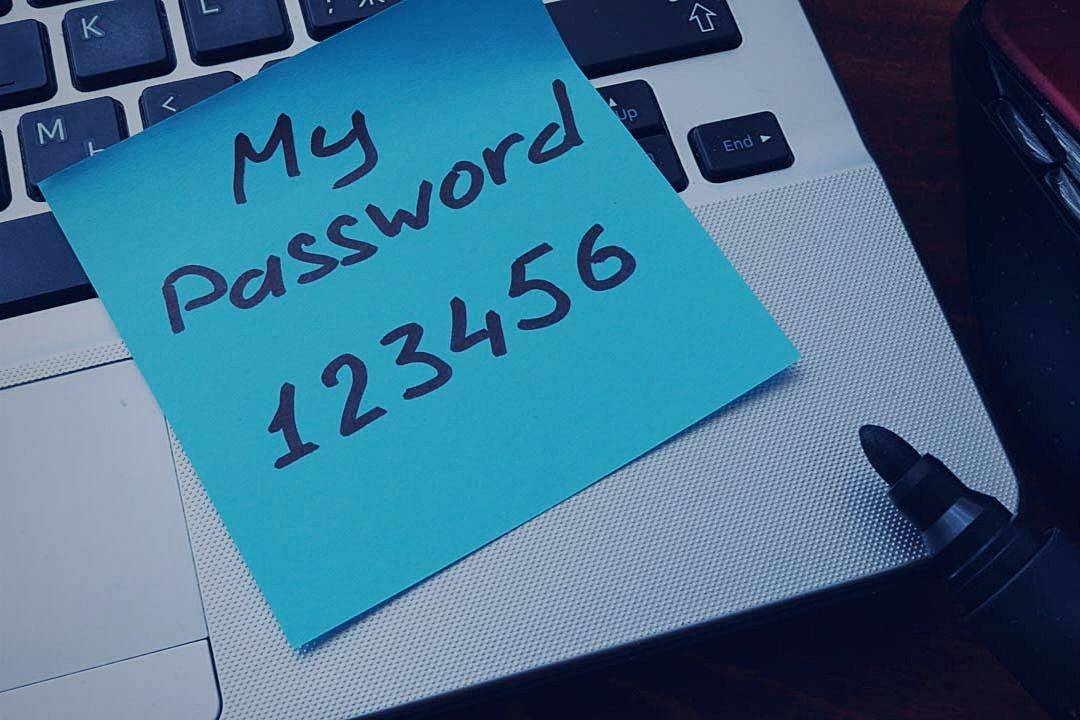 weak password written on note stuck to laptop