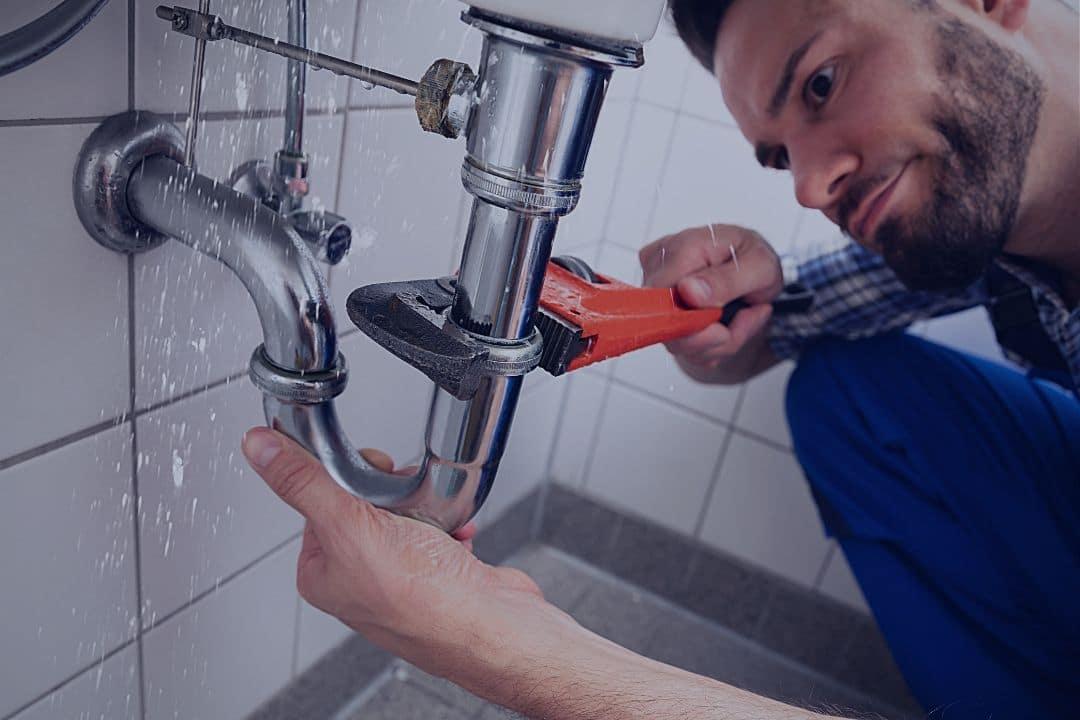 Man fixing leaky pipe
