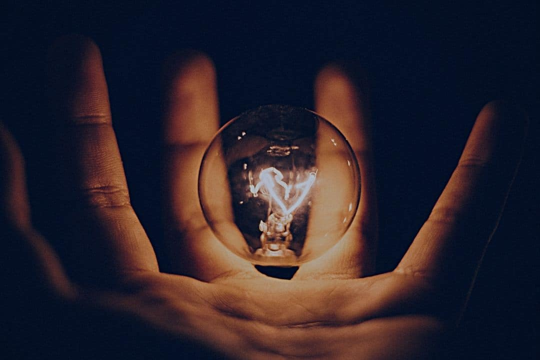light bulb sitting in palm of human hand