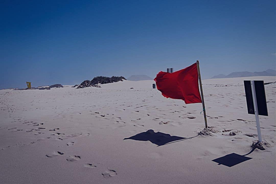 Red flag waving on beach