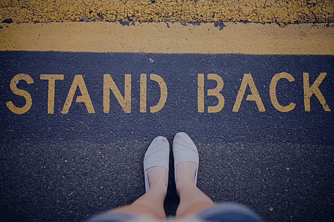 "Woman's feet in font of the words ""Stand back"" written on pavement"