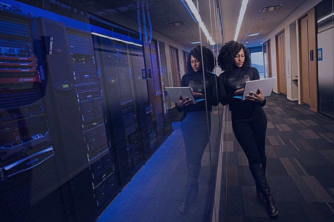 Woman working on computer in server room