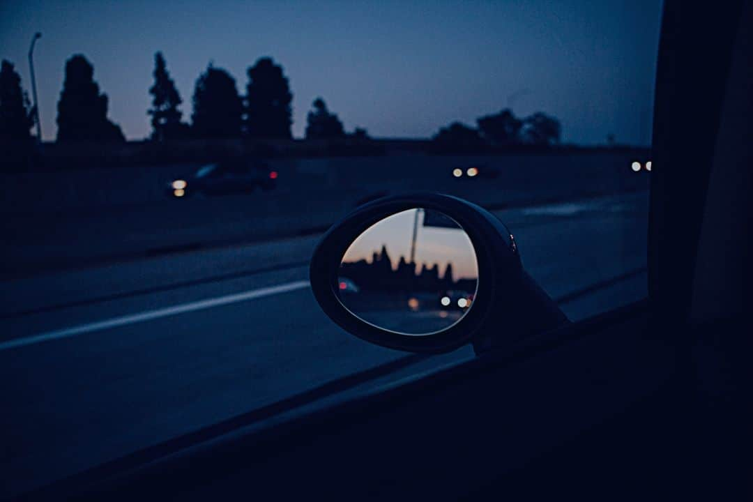 View from side view mirror or car driving at twilight