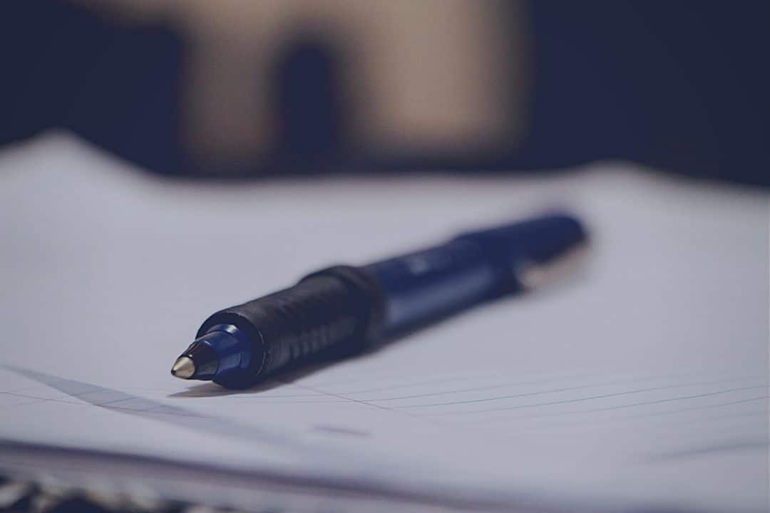 closeup of blue pen sitting on white notebook