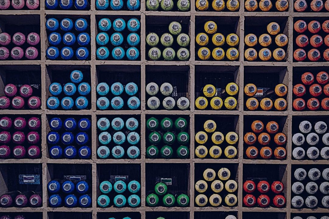Paints organized by color in cabinet